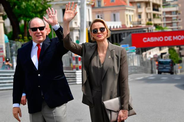 Prince Albert II of Monaco (L) and his wife Princess Charlene of Monaco wave to photographers after meeting members of the Red Cross of Monaco and Italy during a visit ahead of the third practice session at the Monaco street circuit on May 25, 2019 in Monaco, ahead of the Monaco Formula 1 Grand Prix. (Photo by Andrej ISAKOVIC / AFP)